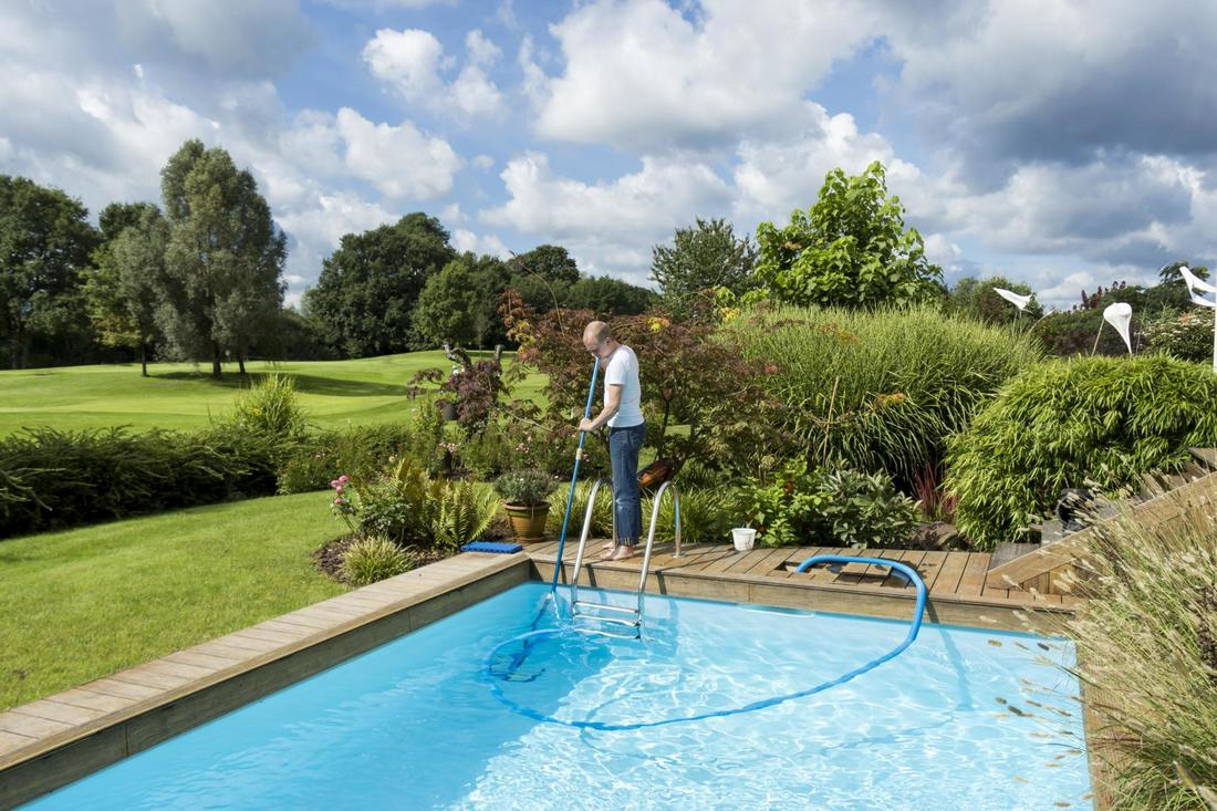 Man performing weekly pool cleaning service